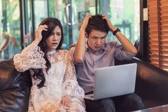 Stressed man and woman using laptop in cafe royalty free stock photo