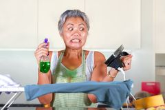 Stressed middle aged Asian woman ironing in stress at home kitchen feeling overwhelmed and tired of working domestic chores in stock photography