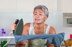 Stressed middle aged Asian woman ironing in stress at home kitchen feeling overwhelmed and tired of working domestic chores in stock photo