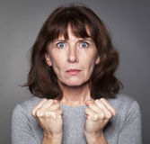 Stressed middle aged lady clenching her fists Stock Photo