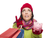 Stressed Mixed Race Woman Holding Shopping Bags and Piggybank Royalty Free Stock Photography