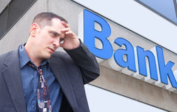 Stressed Money Business Man at Bank. A business man is standing in front of a bank and looks stressed and worried. Can represent finance, the economy, or an Royalty Free Stock Photo
