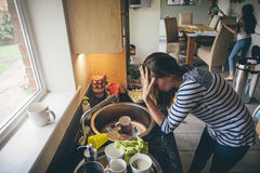 Stressed mother of three. Stressed mum at home. She has her head in her hands at a messy kitchen sink and her children are running round in the background Stock Photos