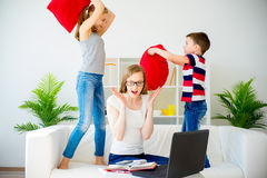 Stressed mother working from home. While her children pillow fight Royalty Free Stock Image