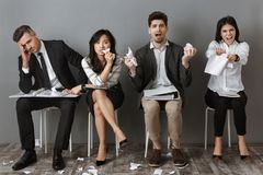 Stressed multicultural business people with folders and notebooks waiting. For job interview royalty free stock image