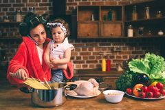 Stressed mum at home. Young mother with little child in the home kitchen. Woman doing many tasks while looks after her stock images