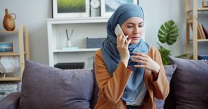 Stressed Muslim woman in hijab talking on mobile phone with worried face at home. Stressed Muslim woman in hijab is talking on mobile phone with worried face stock video footage