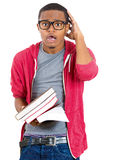 Stressed nerdy guy holding books Royalty Free Stock Image