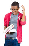 Stressed nerdy guy holding books Stock Photography