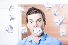 Stressed office employee with scrunched up paper document in mouth. Work disaster Stock Image