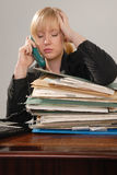Stressed office executive on phone. Stressed young lady office executive on telephone with huge stack of paperwork stock image
