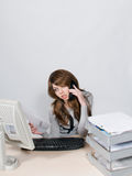 Stressed office worker. Girl sitting at desk on telephone reading papers Royalty Free Stock Photography