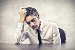 Stressed Office Worker. Stressed and tired office worker leaning on his desk Royalty Free Stock Photos
