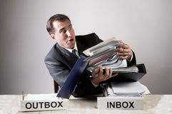 Stressed office worker with a paper stack Royalty Free Stock Image