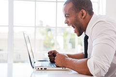 Stressed office worker. Side view of furious young African man in shirt and tie shouting while looking at laptop while sitting at his working place Stock Images