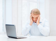 Stressed old man filling a form at home Stock Image