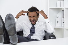 Stressed out African American manager. Portrait of a tired African American businessman who is having a terrible headache and is stressed out. He is sitting in Stock Image