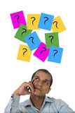 Stressed out business executive against question mark signs Royalty Free Stock Photography