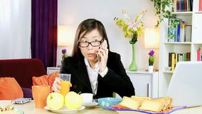 Stressed out business woman at home with 2 cell phones stock footage
