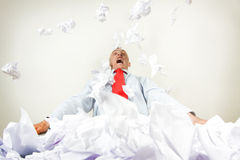 Stressed out businessman. A stressed out businessman being buried by papers stock photo