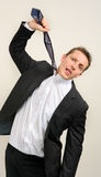 Stressed out businessman. Young white professional pulls his tie to choke himself due to the stressful work environment royalty free stock photo
