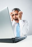 Stressed Out Businessman. Stressed business man sitting at his desk, panics in front of his computer Royalty Free Stock Photography