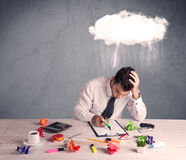 Stressed out businessman at office desk. An elegant office worker is having a bad day while working, illustrated by a white cloud above his head with heavy rain Stock Images