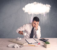 Stressed out businessman at office desk. An elegant office worker is having a bad day while working, illustrated by a white cloud above his head with heavy rain Royalty Free Stock Image