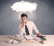Stressed out businessman at office desk. An elegant office worker is having a bad day while working, illustrated by a white cloud above his head with heavy rain Royalty Free Stock Images