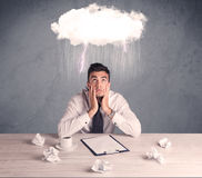 Stressed out businessman at office desk. An elegant office worker is having a bad day while working, illustrated by a white cloud above his head with heavy rain Royalty Free Stock Photography