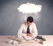 Stressed out businessman at office desk. An elegant office worker is having a bad day while working, illustrated by a white cloud above his head with heavy rain Stock Image