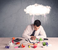 Stressed out businessman at office desk. An elegant office worker is having a bad day while working, illustrated by a white cloud above his head with heavy rain Royalty Free Stock Photo