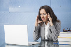 Stressed out businesswoman. Young businesswoman in office with problem Stock Photography