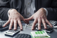 Stressed out financial manager with a bunch of calculators Stock Images
