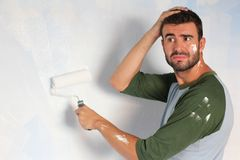 Stressed out male painting his home with space for copy.  Royalty Free Stock Photography