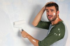 Stressed out male painting his home with space for copy.  Royalty Free Stock Image