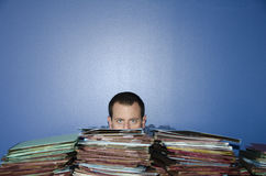 Stressed out man at work behind a pile of files. Man peeking over a pile of files due to boredom at work Royalty Free Stock Images
