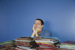 Stressed out man at work. Man with both hands on cheeks while looking straight ahead  to with a pile of files in front of him Stock Photography