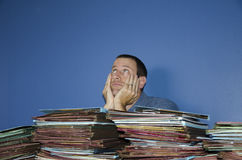Stressed out man at work. Man with both hands on cheeks while looking up to the sky with a pile of files in front of him Royalty Free Stock Photo