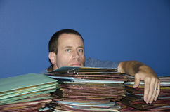 Stressed out man at work. Man with chin on a pile of files while looking straight ahead Stock Images