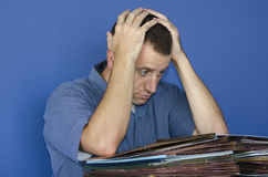 Stressed out man at work in front of a pile of files. Stock Photos