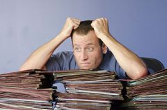 Stressed out man at work pulling his hair out. Stressed out man at work pulling his hair out while leaning on a pile of files Stock Image
