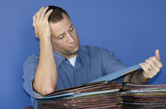 Stressed out man at work reading through files. Stressed out man at work going through piles of files while leaning his head on his hand Stock Image