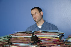 Stressed out man at work staring off into space. Stressed out man at work staring off into space while sitting in front of a pile of files Stock Images
