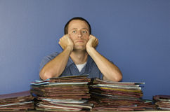 Stressed out man at work staring into space. Man with hands on his face staring off into space at work leaning on a pile of files Royalty Free Stock Photos