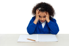 Stressed out primary girl child holding her head. Stressed out primary girl child thinking hard to recollect the answer Royalty Free Stock Image