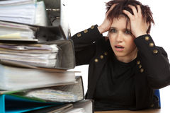 Stressed Out Woman At Work. Stressed Out Worker At Her Desk With Files On White Isolated Background Royalty Free Stock Images