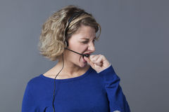 Stressed out young female professional talking with a headset with nervousness Stock Photography