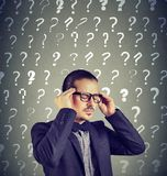 Stressed overburdened young man has too many questions Royalty Free Stock Photo