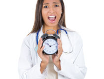 Stressed, overwhelmed female doctor , screaming, holding alarm clock in her hands Stock Image